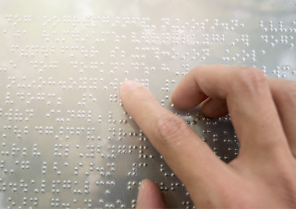 Close up of finger touching braille code