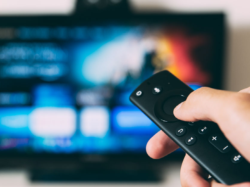 Person holding remote control in front of television.