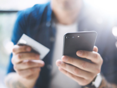 Man holding a phone in one hand and a credit card in another