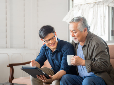 Son helping father use a tablet device