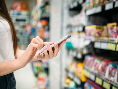 Woman using her phone in a supermarket