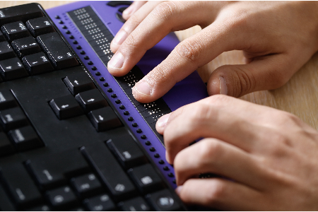 person using a braille reader with a keyboard