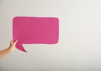 Pink speech bubble against grey background