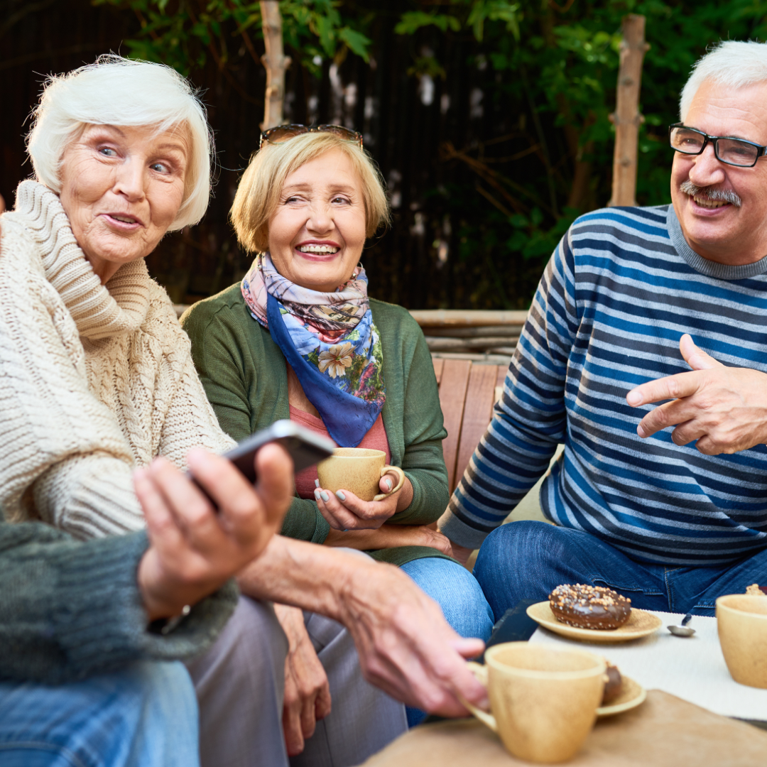 A group of three older adults talking and having coffee